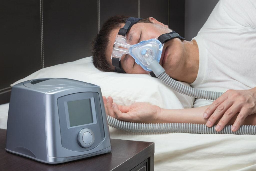 man sleeping with CPAP machine