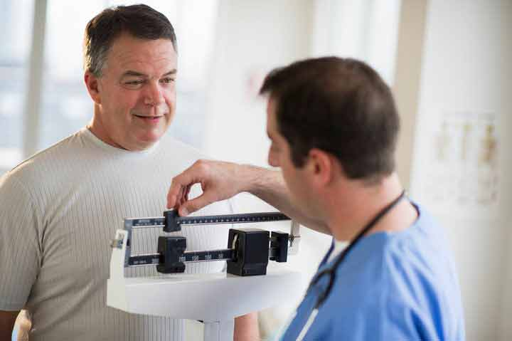 man-being-weighed-at-doctors-office